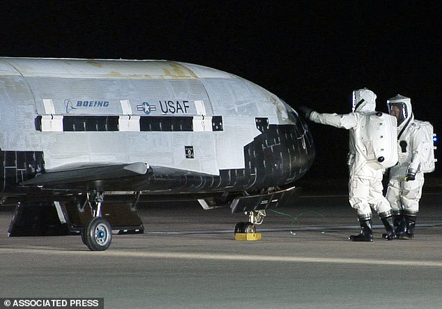 This December 3, 2010, image by the Vandenberg Air Force Base shows technicians examining the X-37B unmanned spaceplane shortly after landing at Vandenberg Air Force Base, California