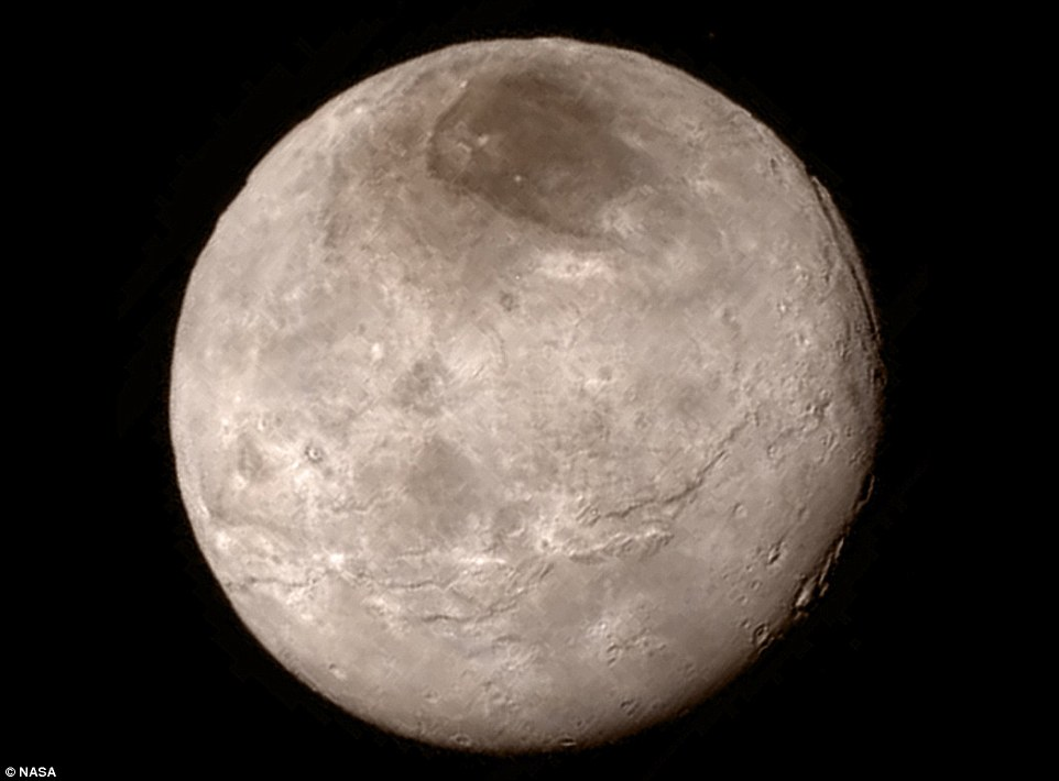 The first images of Charon, showing an area called Mordor, the darkest area near the North pole. A swath of cliffs and troughs stretches about 600 miles (1,000km) from left to right, suggesting widespread fracturing of Charon's crust, likely a result of internal processes. At upper right, along the moon's curving edge, is a canyon estimated to be 4 to 6 miles (7 to 9km) deep