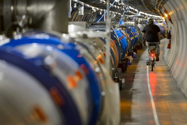 A worker rides his bicycle in a tunnel alongside the European Organisation for Nuclear Research (CERN) Large Hadron Collider (LHC) in Meyrin, near Geneva during maintenance works.