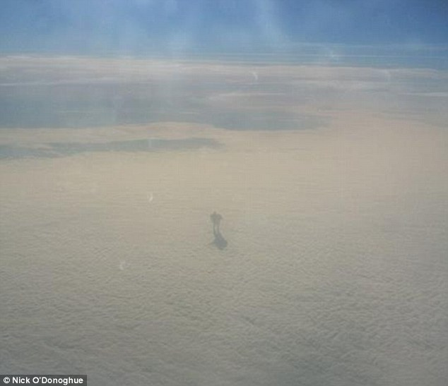 An extraordinary picture captured by a plane passenger at 30,000ft shows what looks like a huge robot walking along the clouds