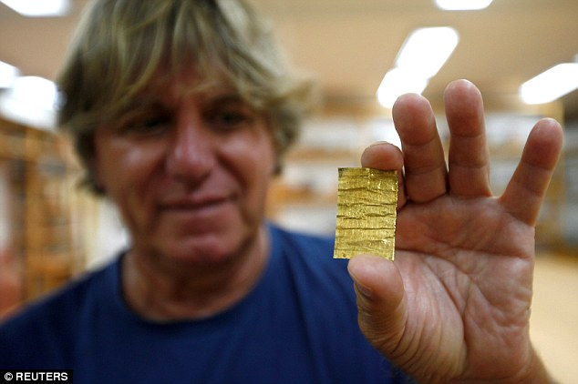 Archaeologists are trying to decipher 'magic spells' etched onto tiny rolls of gold and silver that they found alongside skeletons of humans buried almost 2,000 years ago. Miomir Korac, chief archaeologist at the Belgrade archaeology institute holds the golden amulet